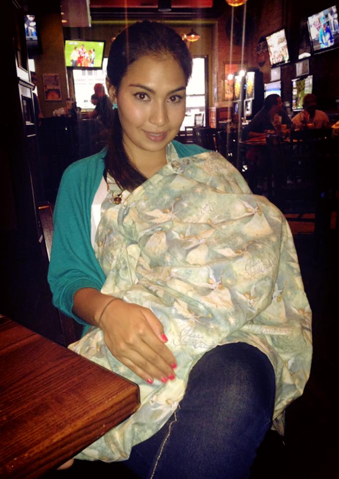 Badass Breastfeeder Secenas using a nursing cover while breastfeeding in public.
